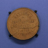 """Wooden medallion (2 3/8'' diam.) commemorating the National Peace Jubilee, Boston. Front, relief carving of """"The Great Coliseum for the National Peace Celebration."""" Back, """"National Peace Jubilee Association, Boston, June 1869"""""""