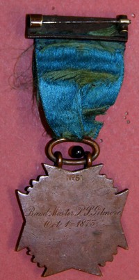 "Medal (bronze, 1 5/8'' square cross) suspended on blue ribbon from bronze bar. Medal bear motto, ""For long service, 22''; bar bears word, ""Defendam."" Back of medal is inscribed ""Band Master P.S. Gilmore, Oct. 1- 1873"""
