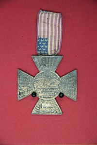 """Medal (2'' square iron cross) suspended on an American flag ribbon. One side bear in center, """"World's Peace Jubilee, Boston, 1872""""); the reverse has the names of countries and the words """"Projector"""" and """"Conductor"""" on the four arms"""