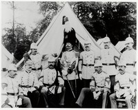 Photograph (17''x20'') of Gilmore and band of 9 players (without instruments) seated and standing in front of a tent in a natural setting. Gilmore wears full regalia, including plumed beaver hat. No photographer or date. Mounted in tag board