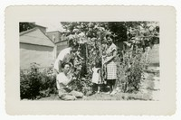 Two Men, Woman, and Child in Garden [Photograph, Black and White] [Notebook 2]