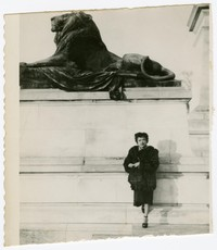 Fermina Santos Peji in front of lion statue [Photograph, Black and White] [Digital Only]