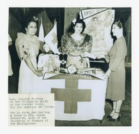 Mrs. Calabia at the Philippine Booth for the American Red Cross at the Statler Hotel, handing a check to Mrs. Jaime Hernandez [Photograph, Black and White] [Notebook 1], circa 1940s