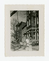 Julie Panganiban Holding Lena Panganiban on Sidewalk in Front of Their Apartment [Photograph, Black and White] [Notebook 2], February 16, 1948