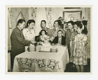 Leona Puyot and a Man Cutting a Cake with a Group including Mr. and Mrs. Joe Puyot [Photograph, Black and White] [Notebook 2], circa 1945-1950