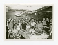 Group (including Mrs. Aqui, Joe Puyot, Mrs. Joe Puyot and Toribia Sales) around table with food at party [Photograph, Black and White] [Notebook 2], December 1943