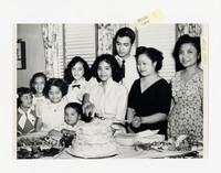 Leona Puyot (right) with Mina Puyot (center) and a Group including Children and Cake [Photograph, Black and White] [Notebook 2], circa 1955-1960