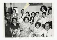 Leona Puyot and Mina Puyot with a group and presents [Photograph, Black and White] [Notebook 2], circa 1955-1960