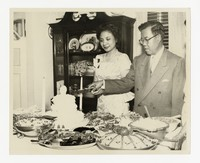 Leona Puyot and Lucelo Puyot Cutting Cake [Photograph, Black and White] [Notebook 2], circa 1950-1960