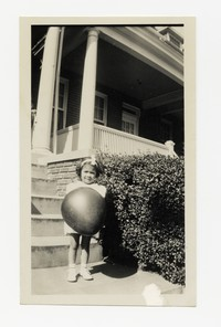 Unknown Girl with Large Ball Outside of a House [Photograph, Black and White] [Notebook 2], circa 1940-1960