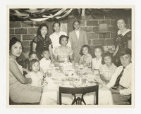 Leona Puyot with a Group at a Table [Photograph, Black and White] [Notebook 2]