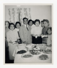 Group of Nine Individuals, including Leona Puyot and Lena Panganiban Around Table [Photograph, Black and White] [Notebook 2], circa 1950-1960