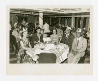 Group at Dinner with Hats [Photograph, Black and White] [Notebook 2], circa 1950-1960