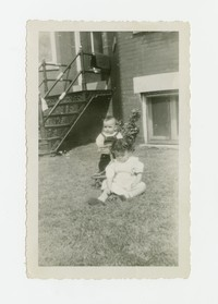 Two small children playing in a yard [Photograph, Black and White] [Box 2, Black Photograph Box], circa 1950