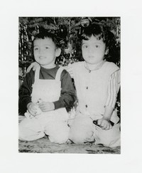 A small girl and boy sitting in front of a Christmas tree [Photograph, Black and White] [Box 2, Black Photograph Box], circa 1950