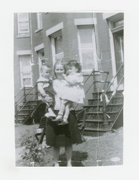 Woman holding two children in front of row house [Photograph, Black and White] [Box 2, Black Photograph Box], circa 1950