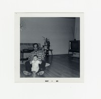 Felipe Mondoñedo with a baby sitting on the floor [Photograph, Black and White] [Box 2, Black Photograph Box], May 1965