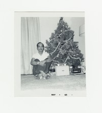 Felipe Mondoñedo sitting next to a Christmas tree [Photograph, Black and White] [Box 2, Black Photograph Box], December 1964