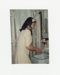 Nita Mondoñedo at a sink in a bathroom [Photograph, Color] [Box 2, Black Photograph Box], circa 1965-1970