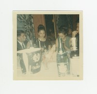 Two people and Nita Mondoñedo (right) sitting at a table at an event at the Willard Hotel [Photograph, Color] [Box 2, Black Photograph Box], circa 1970