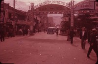 Street scene including an arch, stores, and pedetrian, South Korea, undated
