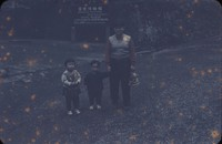 Woman and two children in front of a Nikko Museum sign, undated