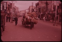 Man pulling cart down commercial street, South Korea, undated